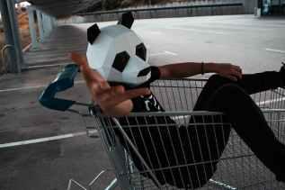 man riding shopping cart